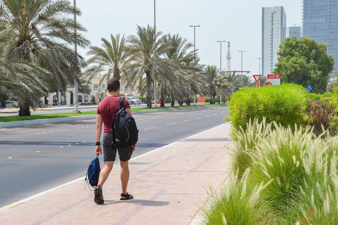 Bartek z dwoma plecakami na ulicy w Abu Dhabi