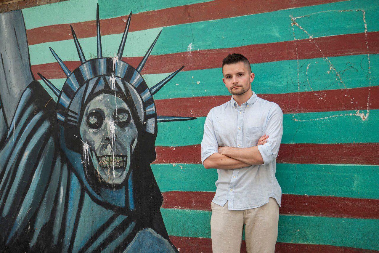 Bartek na tle murala ze Statuą Wolności w Iranie