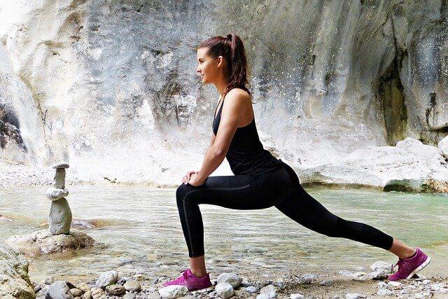 Techniki relaksacyjne a jedna z nich to yoga uprawiana przez kobietę obok zbiornika wodnego