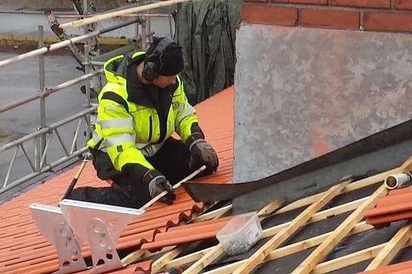 Under en pågående takrenovation tar en snickare ett mått på en tegelpanna.