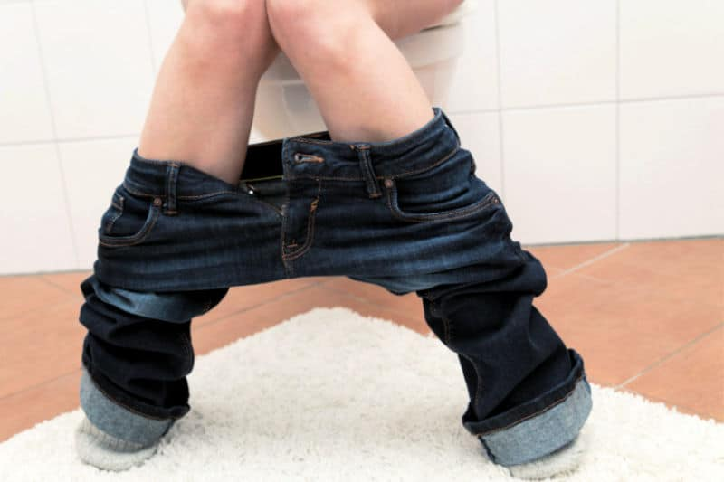 Knees-down photo of person on toilet