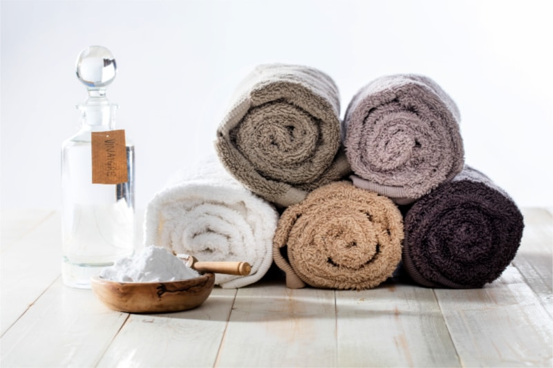Rolled up earth-tone towels next to a bowl of baking soda and a bottle of vinegar to use in laundry
