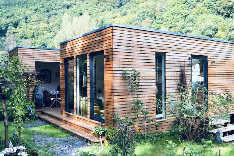 Das Bild zeigt ein Minihaus von Außern. Das Minihaus hat ein Holzfassade. Im Hintergrund des Minihauses sieht man grüne Bäume und Berge.