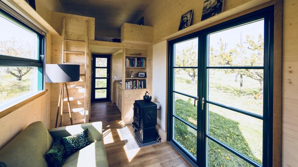 Das Bild zeigt die Innenansicht eines Haus auf Rädern. Man sieht in das Innenleben des Haus auf Rädern. Zu sehen ist ein Loft für den Schlafbereich, ein Sofa, ein Ofen und eine Lampe