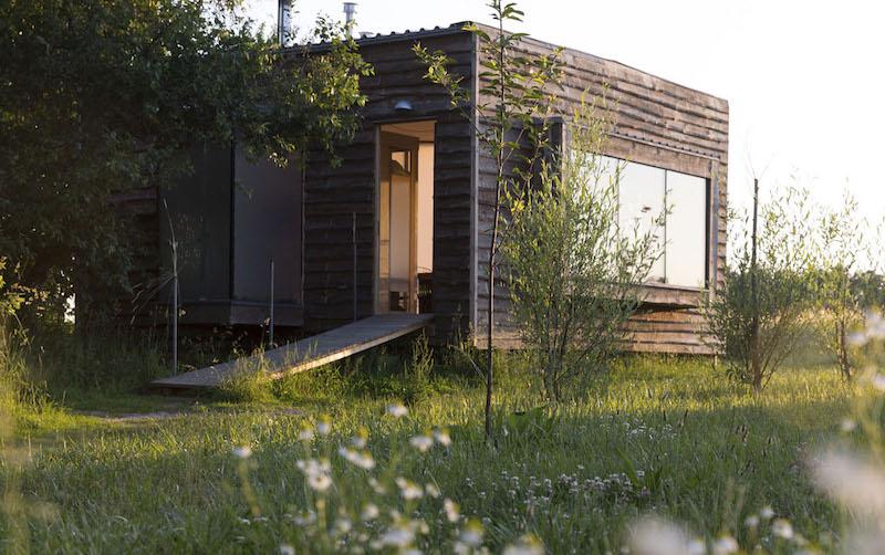 Das Bild zeigt die Fasse eines kleines Hauses auf einer grünen Wiese