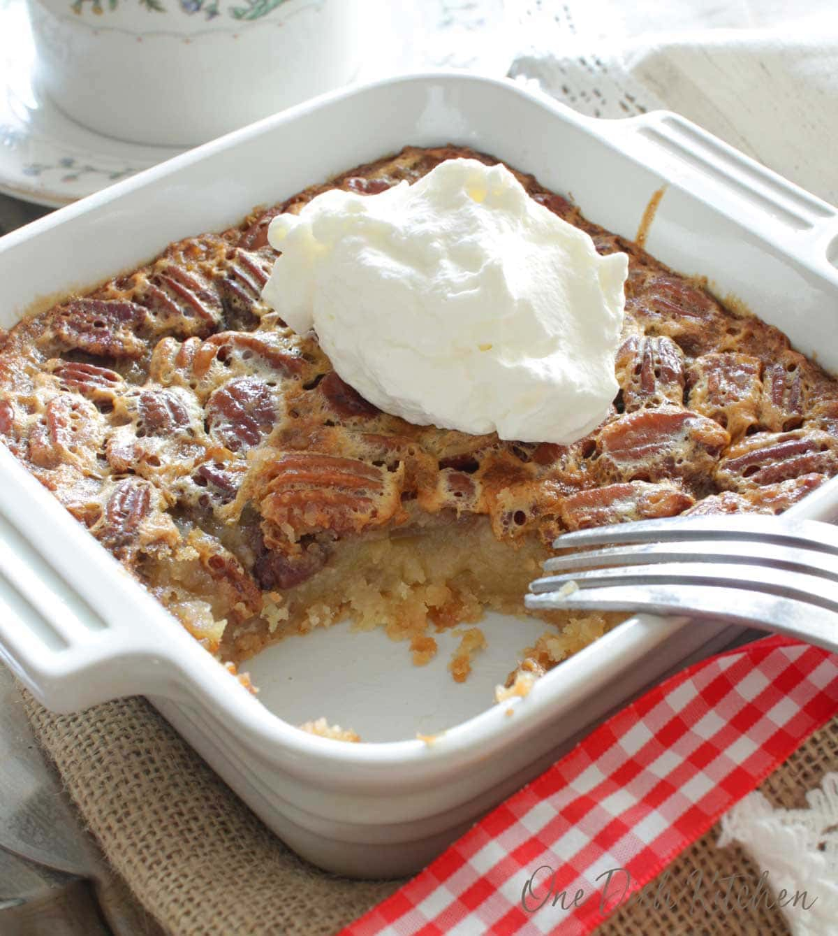 a single serving pecan pie topped with whipped cream and a bit taken out with a fork | one dish kitchen