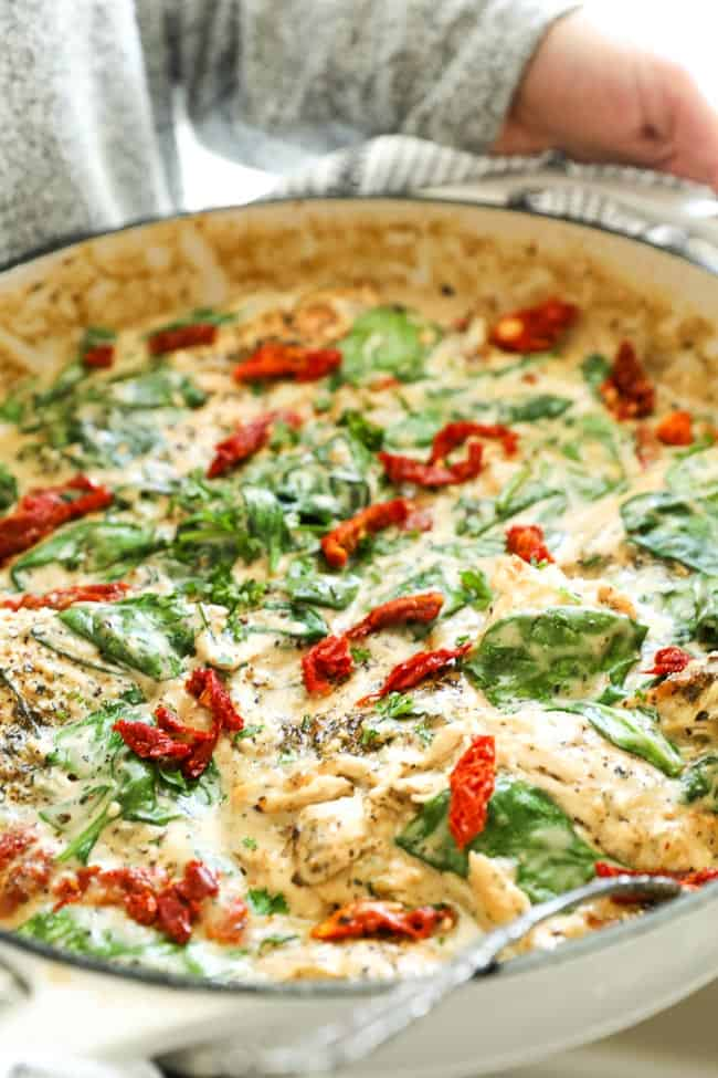 Angled vertical image of holding skillet of creamy tuscan chicken with sun-dried tomatoes and fresh chopped parsley on top.