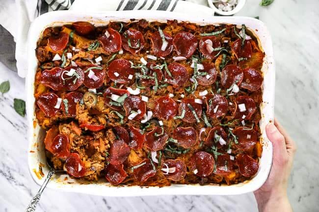 Overhead shot of spaghetti pizza casserole in casserole dish with serving spoon in one corner and holding the dish with one hand.
