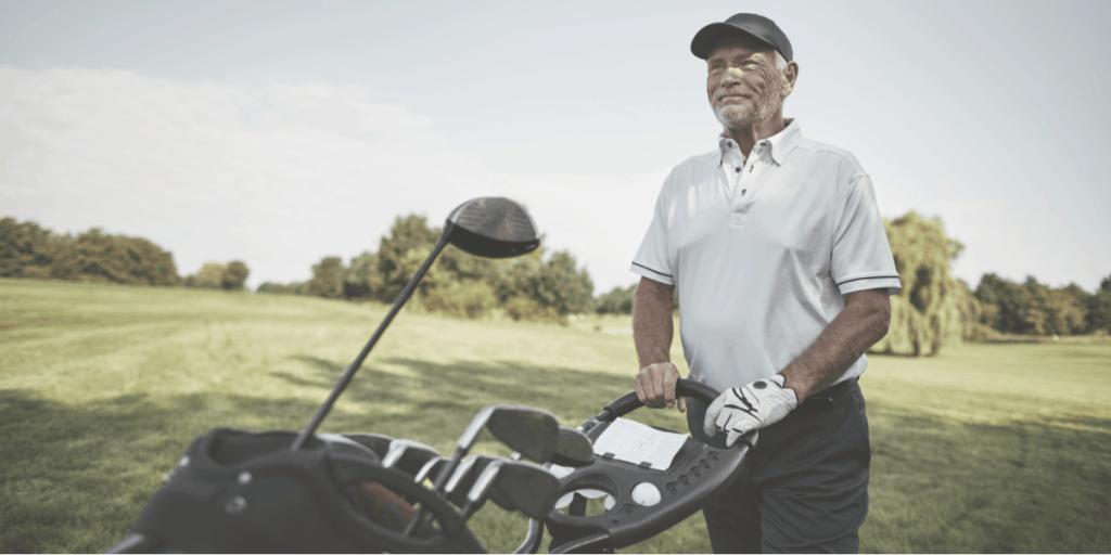 senior golfer push golf bag on golf push cart
