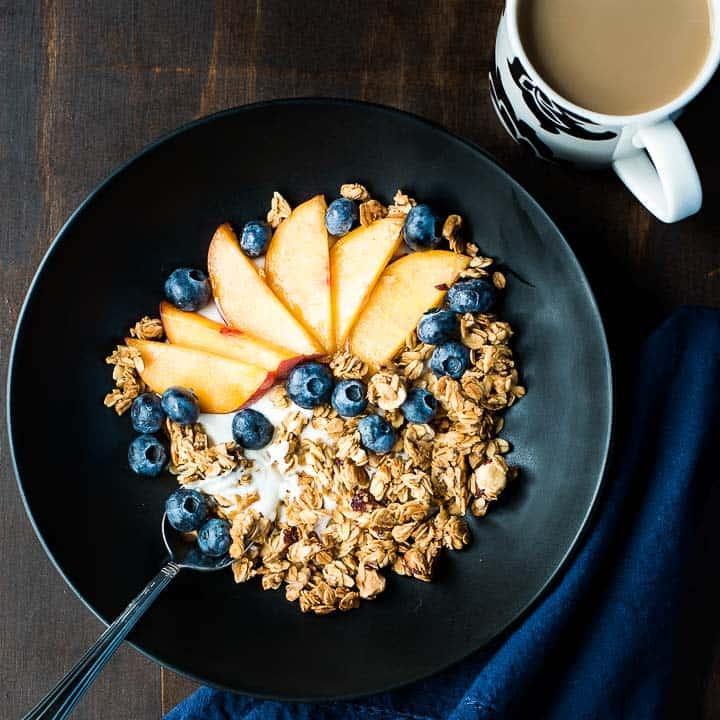 A homemade yogurt parfait with maple hazelnut homemade granola, peaches, and blueberries in a dark bowl.