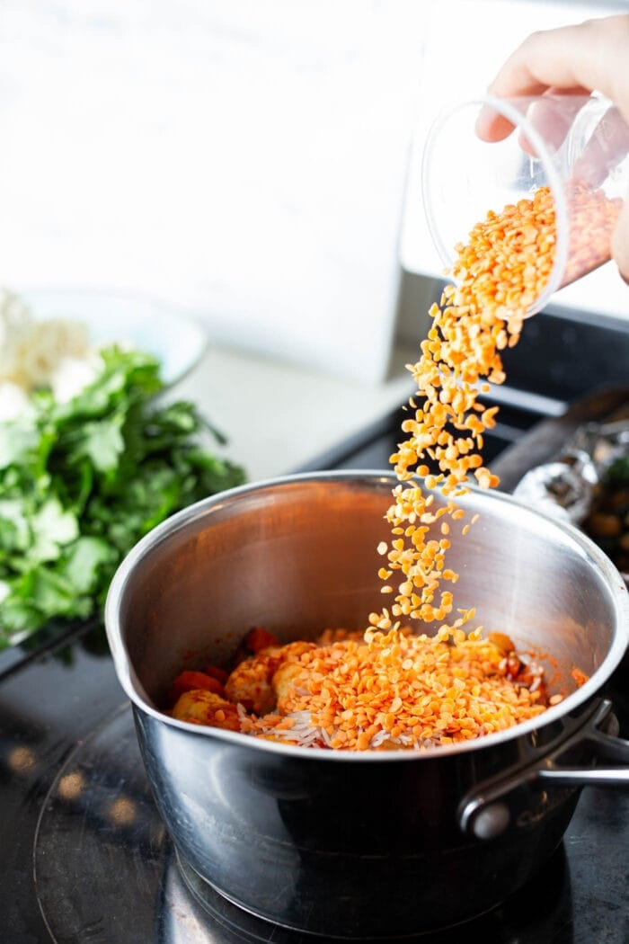 Adding red lentils to a pot of cauliflower curry stew.