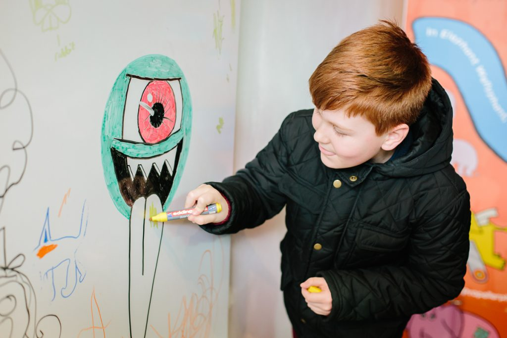 A boy drawing a picture of a green monster with an orange eye.