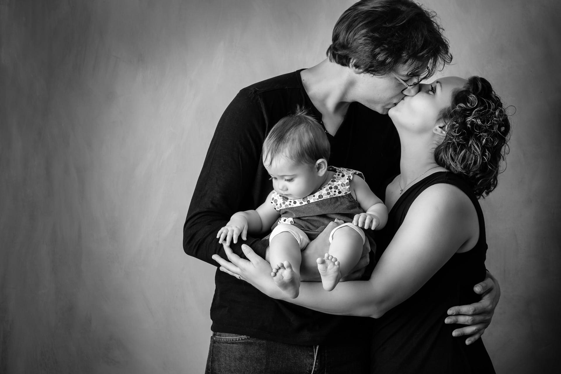 Bébé dans bras des parents en noir et blanc
