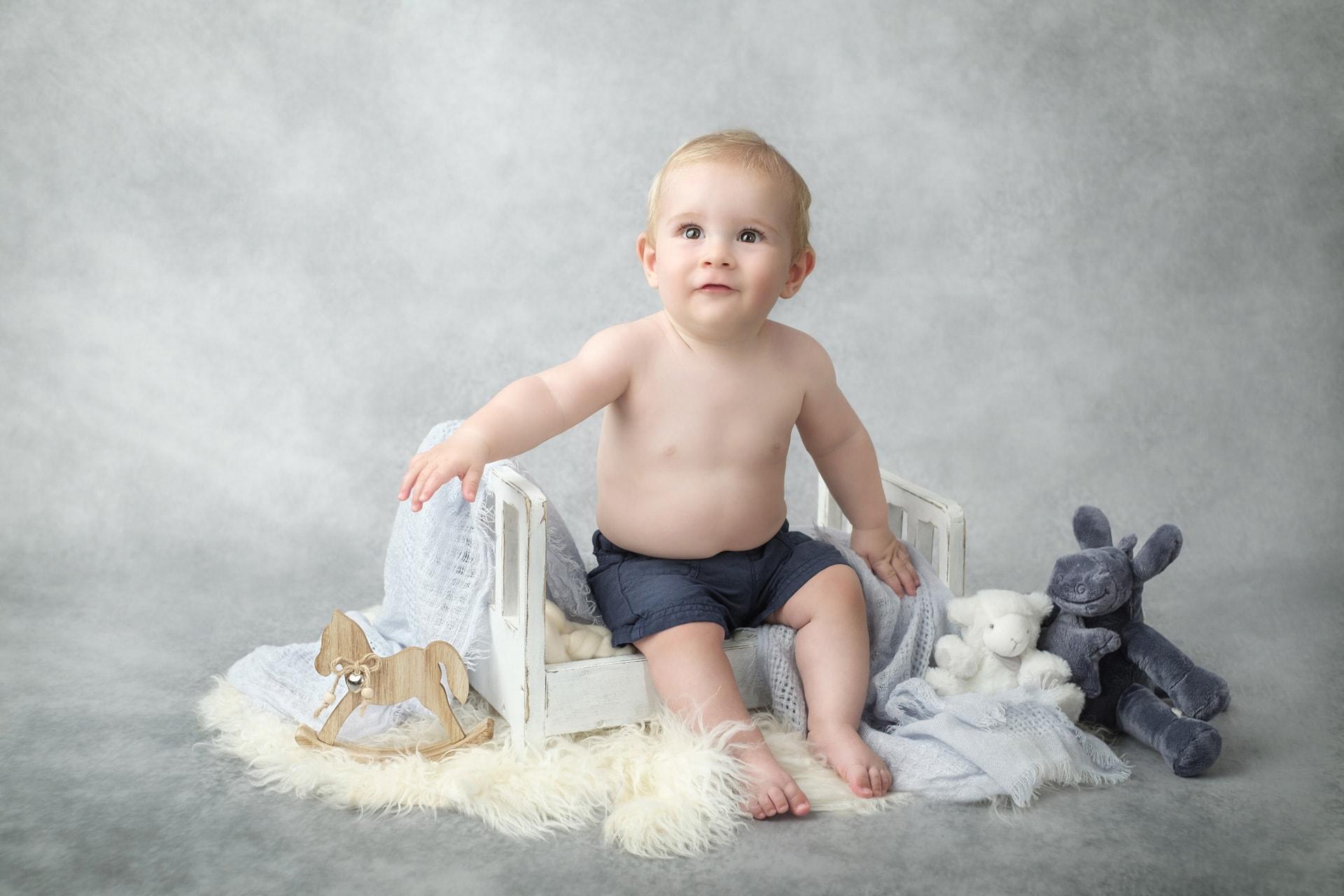 Portrait bébé avec lit en bois et peluche