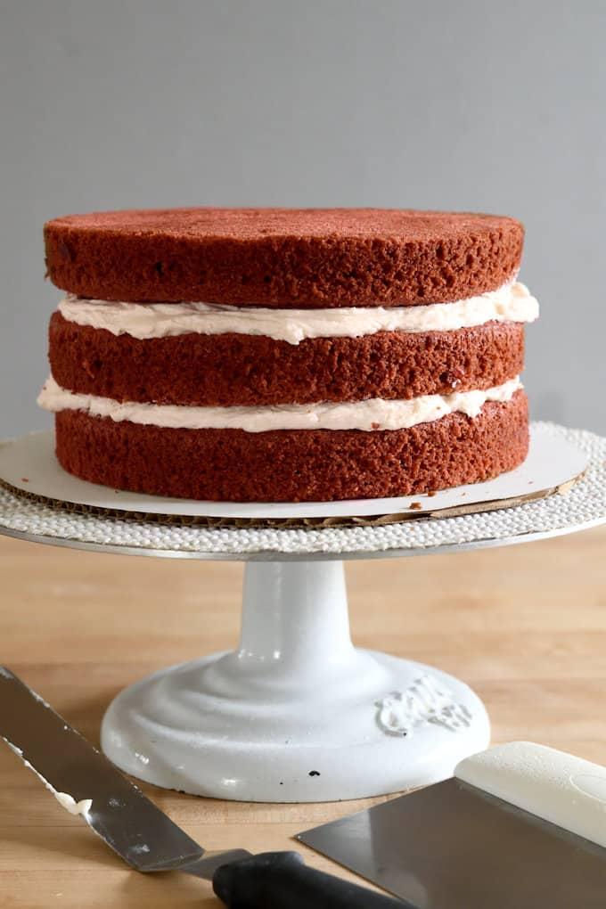 an uniced red velvet cake on a cake turntable