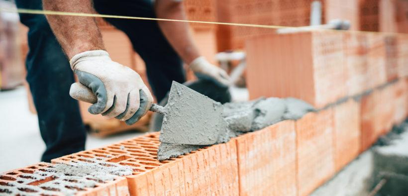 Ein Maurer bedeckt einen Mauerziegel mit Mörtel
