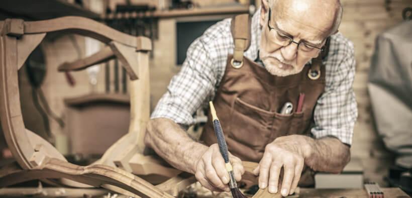 Ein alter Tischlermeister fertigt einen Stuhl an