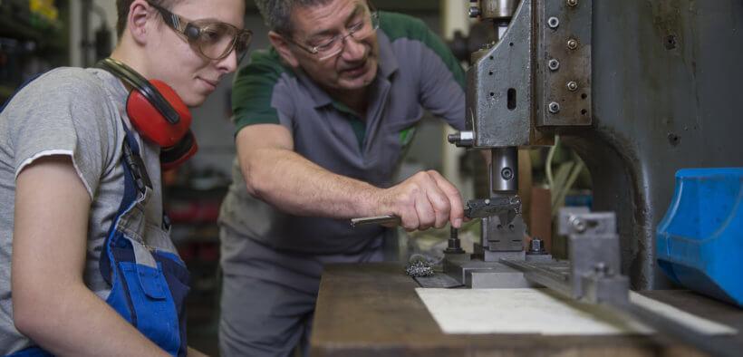 Ein Meister zeigt beim Pflichtpraktikum Arbeitsschritte an einer Maschine