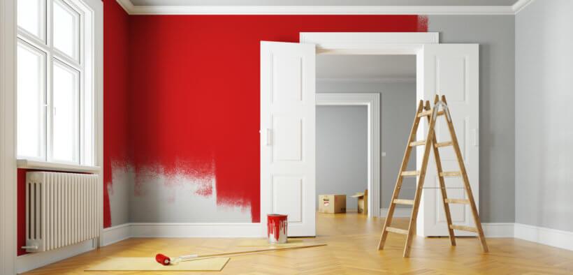 Beim Streichen der Wohnung wird eine Wand mit roter Farbe gestrichen
