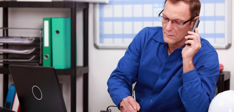 Ein Mechaniker sitzt im Büro und telefoniert