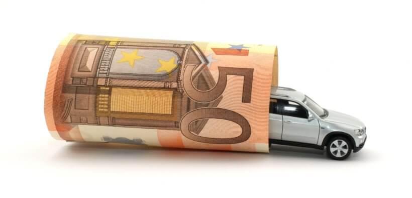 Symboldbild für Fahrtkosten: Ein Spielzeugauto, um das ein 50-Euro-Schein gewickelt wurde