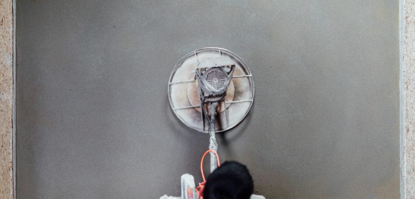 Ein Handwerker wird den Beton schleifen.