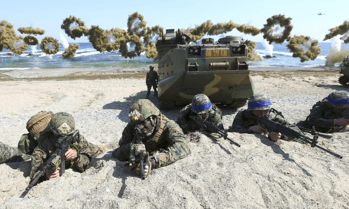FILE - In this March 12, 2016, file photo, Marines of the U.S., left, and South Korea wearing blue headbands on their helmets, take positions after landing on a beach during the joint military combined amphibious exercise, called Ssangyong, part of the Key Resolve and Foal Eagle military exercises, in Pohang, South Korea. The Pentagon on Monday, June 18, 2018,  formally suspended a major military exercise planned for August with South Korea, a much-anticipated move stemming from President Donald Trump's nuclear summit with North Korean leader Kim Jong Un. (Kim Jun-bum/Yonhap via AP, File)