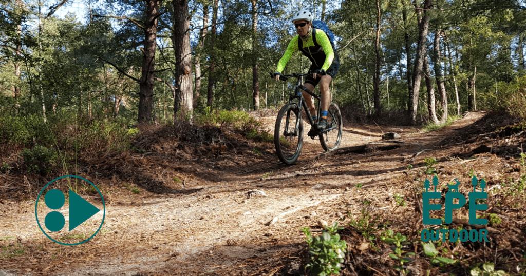 Mountainbiker in het bos tijdens een tocht met privé gids.