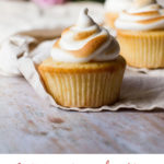 Three cupcakes with torched Swiss meringue, one in focus. Purple roses in the background. Pinterest pin.