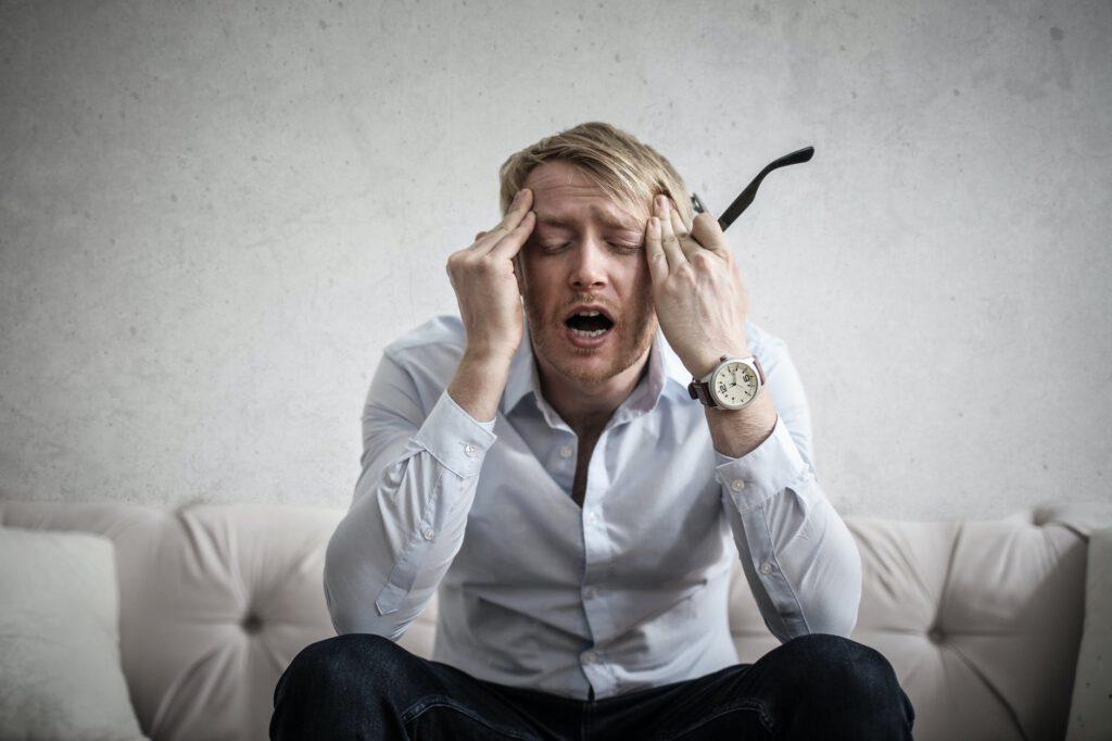 Mann greift sich an den Kopf, weil er Anlegerfehler begangen hat und seine Rendite leidet.