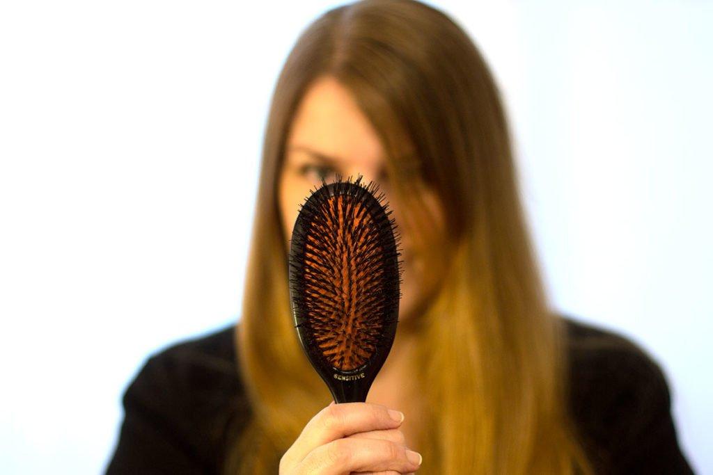 Femme qui tient brosse à cheveux Mason Pearson