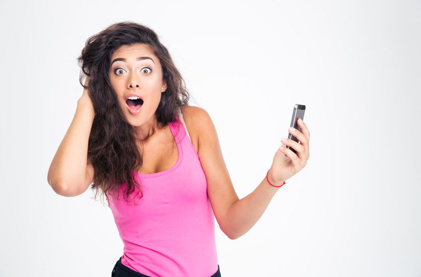 Shocked woman standing with smartphone