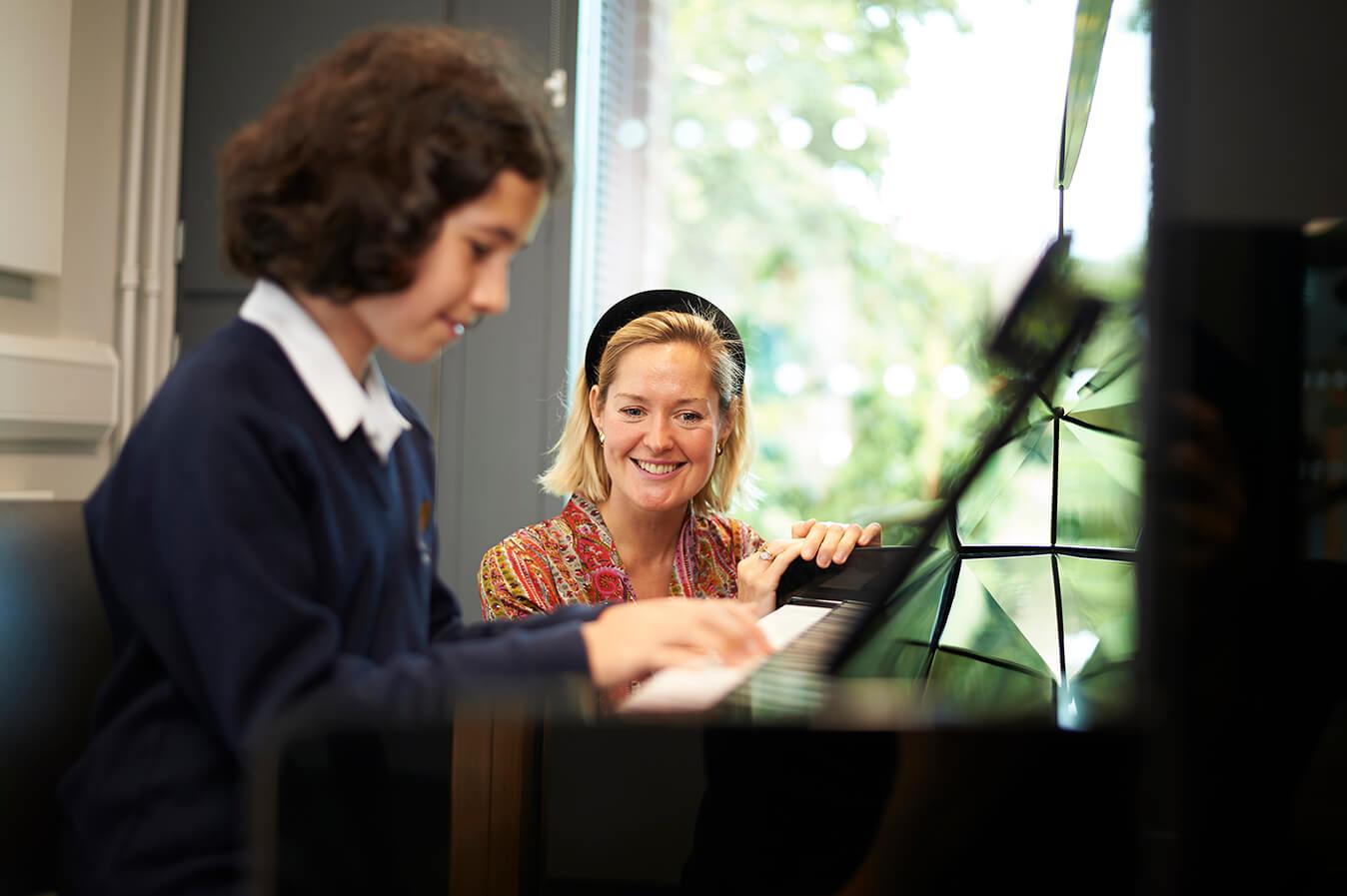 Teacher teaching piano to a girl