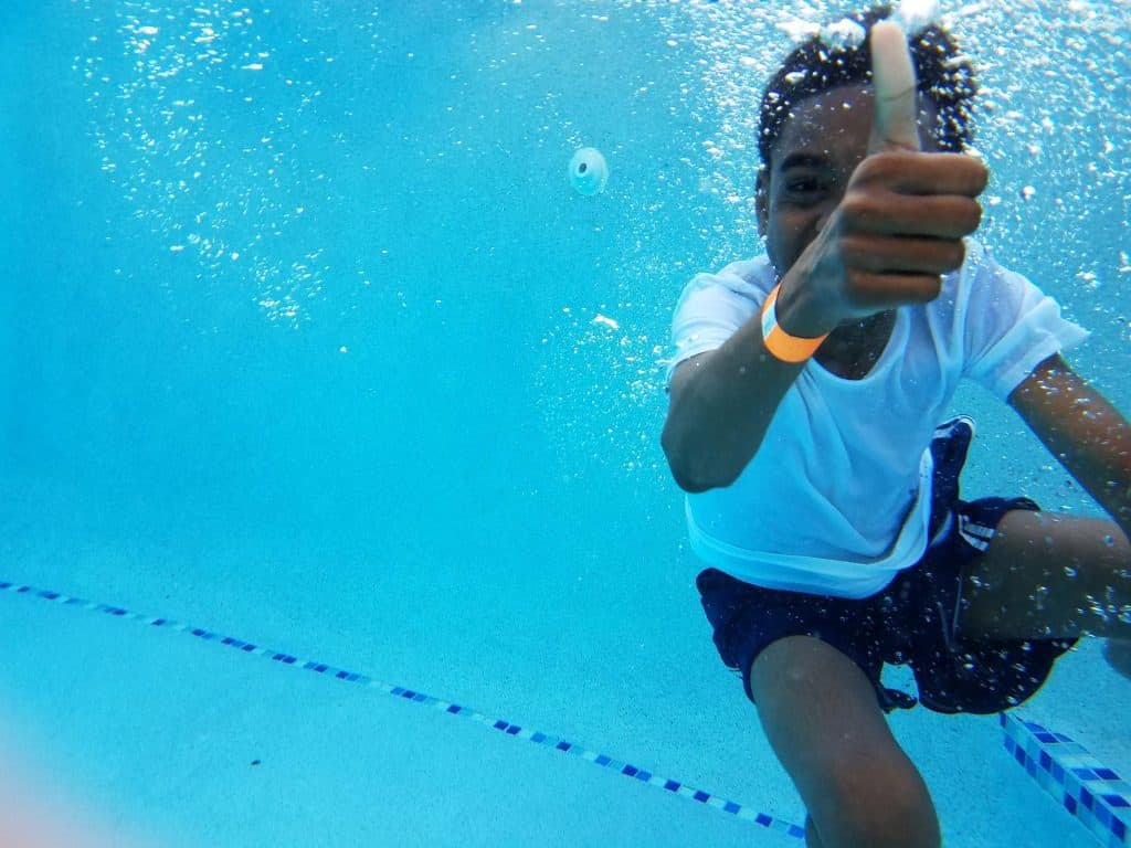 kid with white shirt in swimming pool under water doing a thumbs up