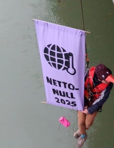 Ein Aktivist hängt von der Salztorbrücke und hisst einen Banner mit der Forderung nach Netto-Null 2025