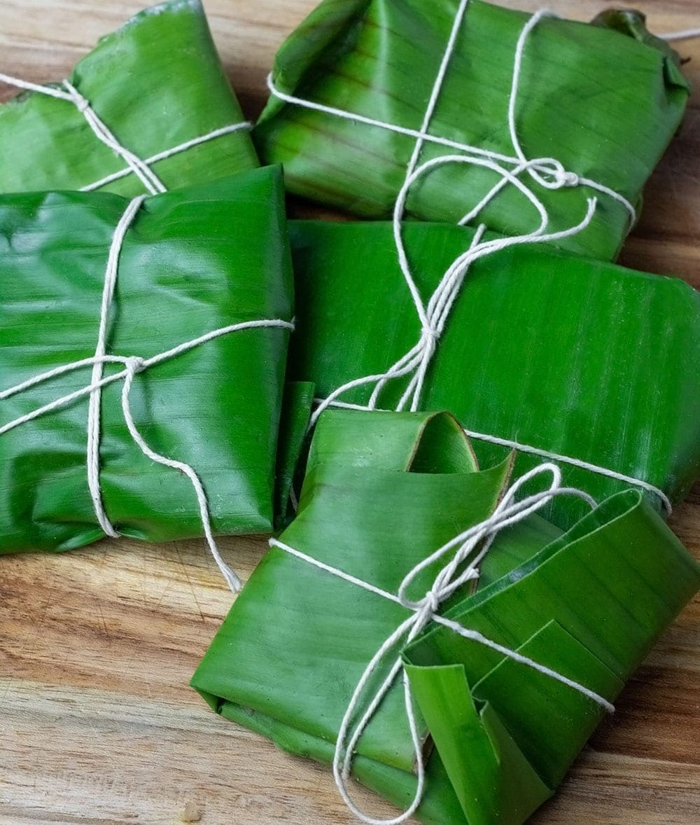 Blue draws wrapped in fresh banana leaves on a wooden cutting board