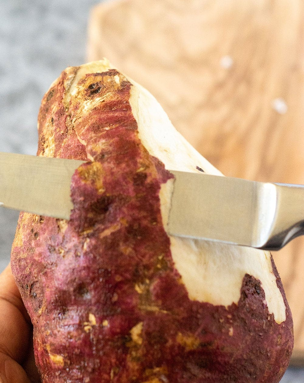 Sweet potato being peeled with a knife