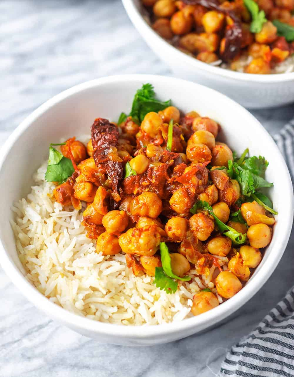 chana masala in a two white bowls on white background