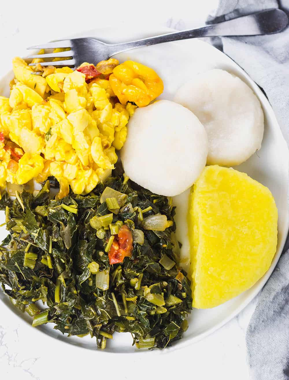 Overhead photo of Jamaican Callaloo served with ackee, boiled dumplings, yellow yam on white plate