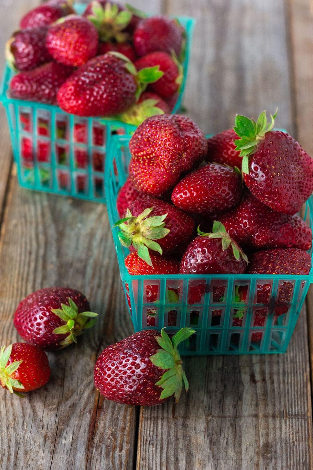 Fresh local strawberries picked from farm near me in green baskets