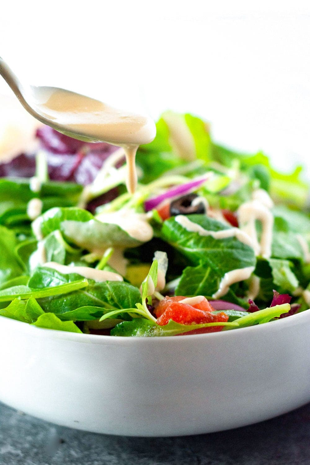 Salad with creamy Asian salad dressing in a white bowl