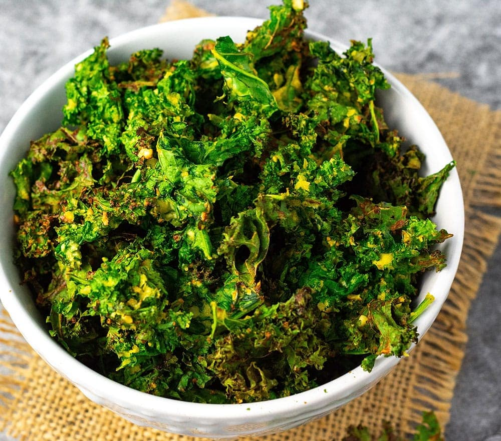 Overhead Air fryer kale chips in a white bowl on a burlap napkin on a gray marble background