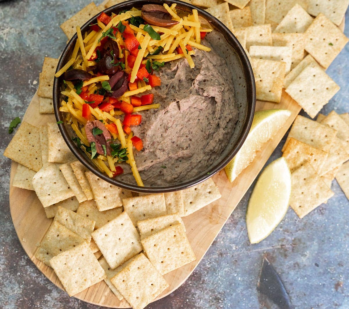 overlay black bean hummus in a brown bowl on a cutting board with crackers on a grey background