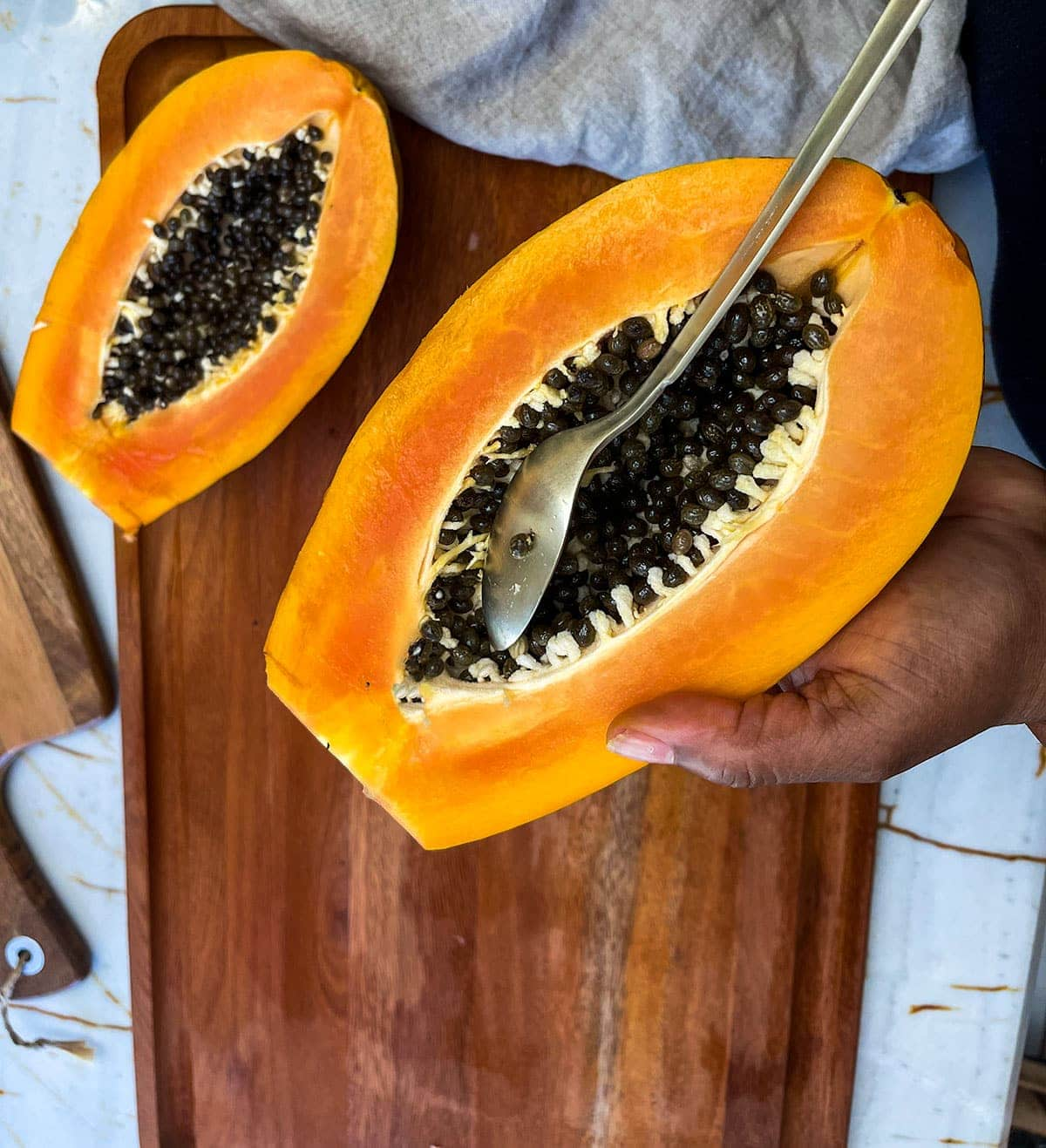 scooping out the seeds of the papaya