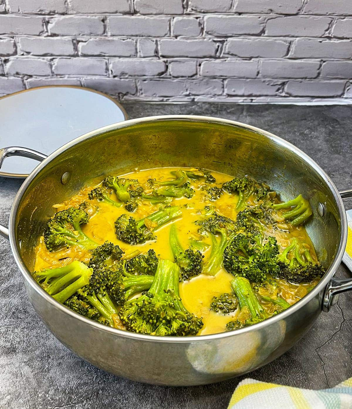 broccoli curry recipe in a silver saucepan on a grey background