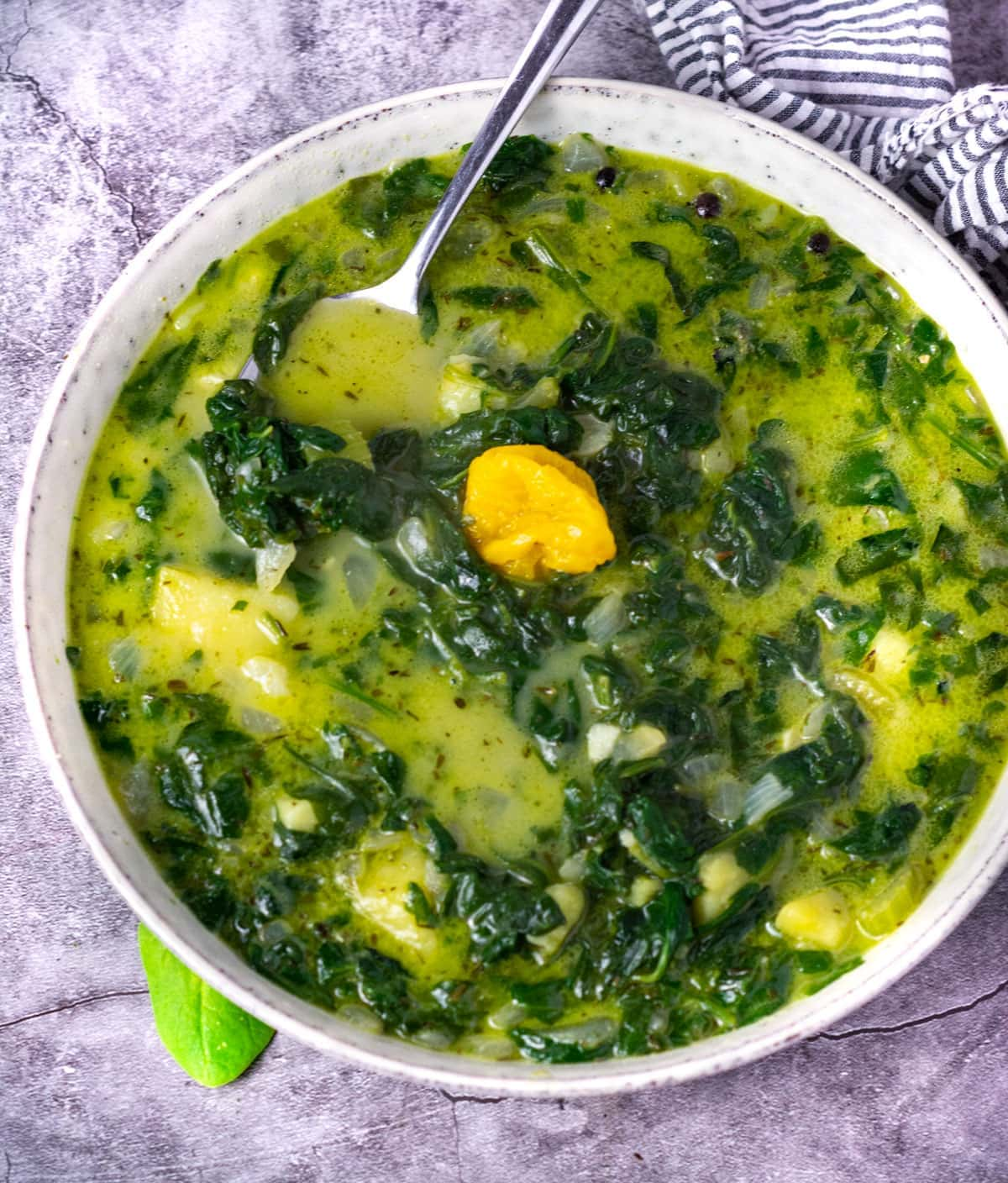 vegan spinach soup with chopped spinach leaves overhead in a beige bowl, overhead on a grey background