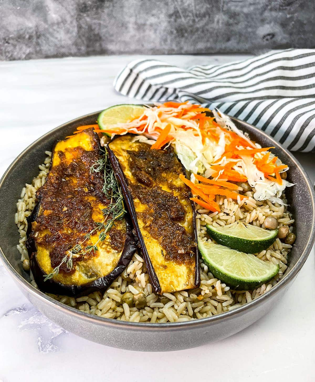 close up broiled eggplant with jerk sauce in a grey bowl with rice and peas and coleslaw