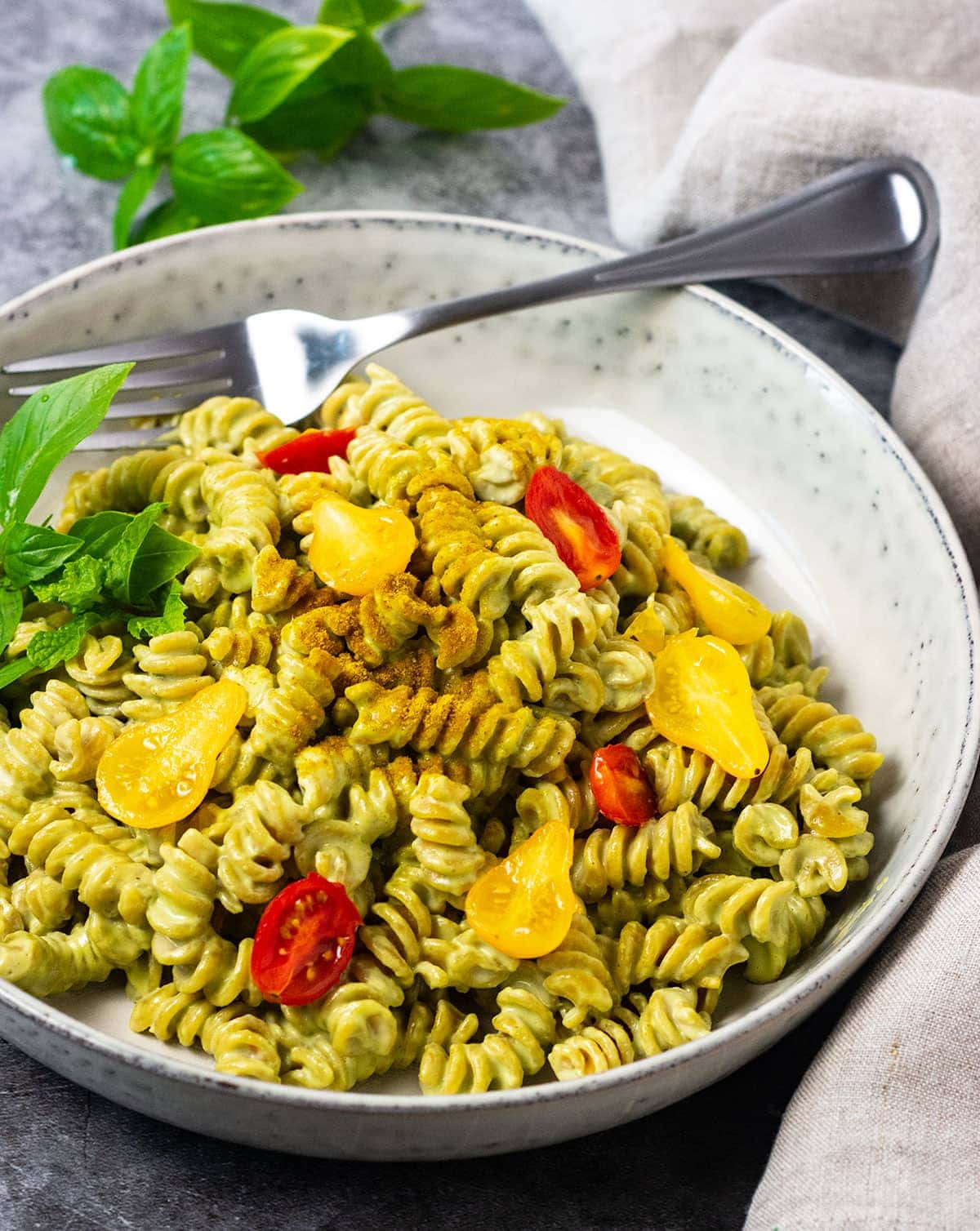 Straight on of creamy vegan pesto pasta in a beige bowl on a grey background with a silver spoon garnished with tomatoes and basil leaves