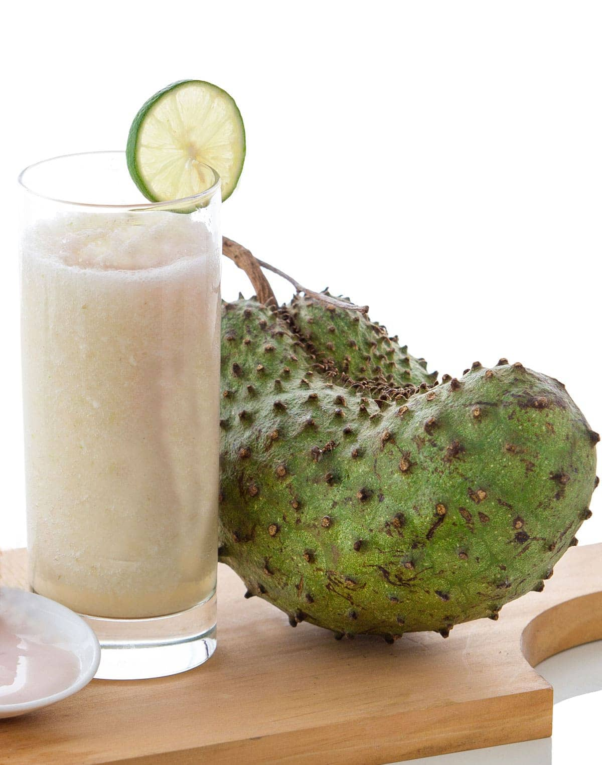 sour sop juice in a glass with a slice of lime, a whole soursop on a cutting board