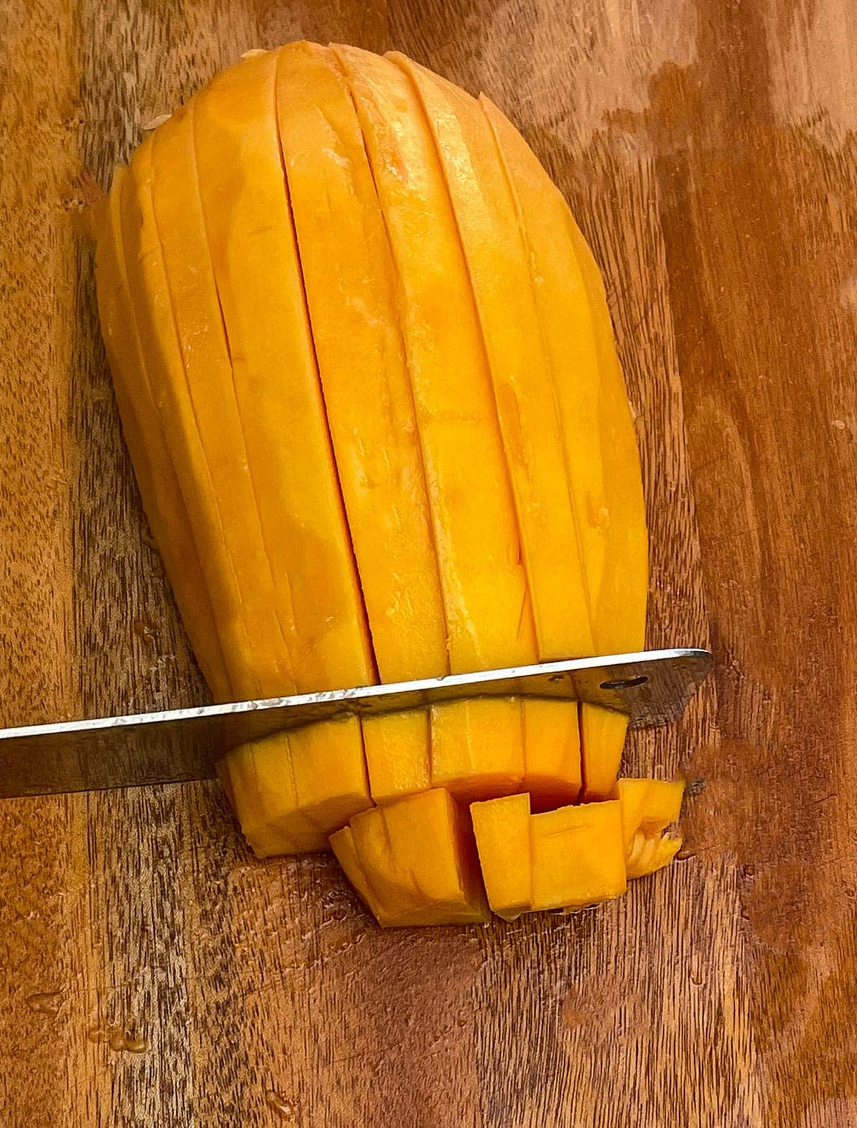 Cubes of papaya on a wooden cutting board